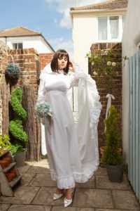 Hire this cute late sixties early seventies wedding dress size 10. Model is approx 5.6 and has two and a half inch heel on.